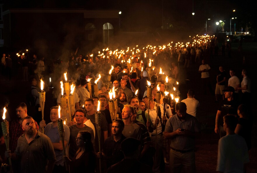White nationalists carry torches on the eve of a Unite The Right rally in Charlottesville, Va., on Aug. 11.
