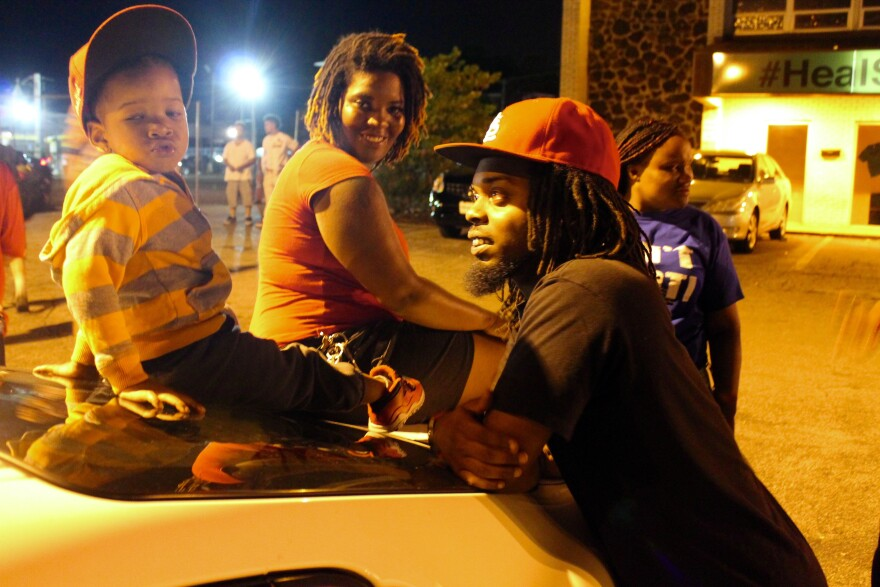 Darnell Wilkes and his son Khalliel wait around at Tuesday's protests along West Florissant Avenue in Ferguson.