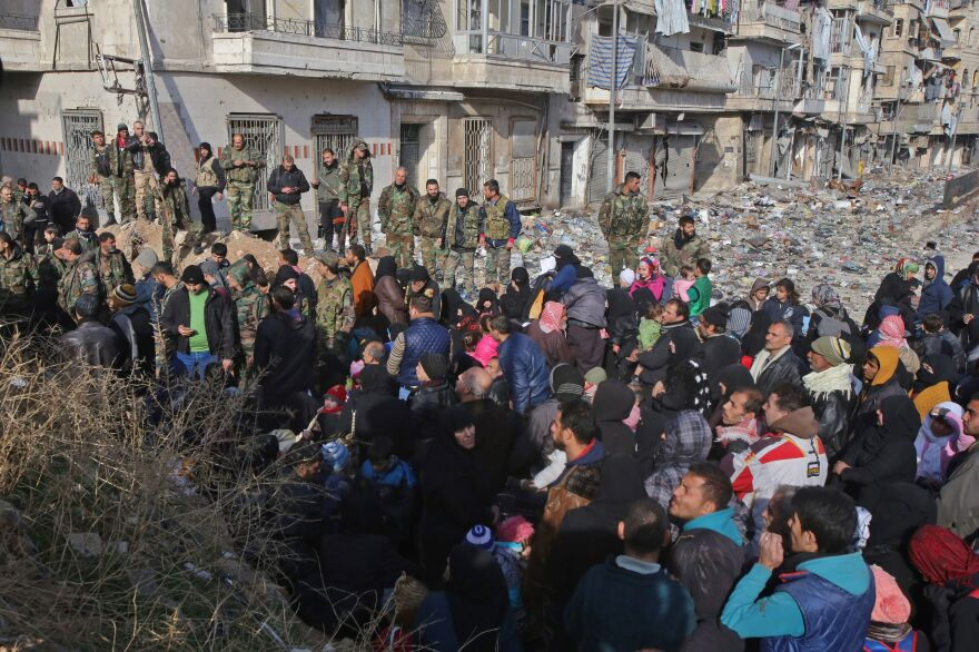 Syrian residents fleeing violence gather at a checkpoint, manned by pro-government forces, in the Maysaloun neighborhood of Aleppo on Thursday.