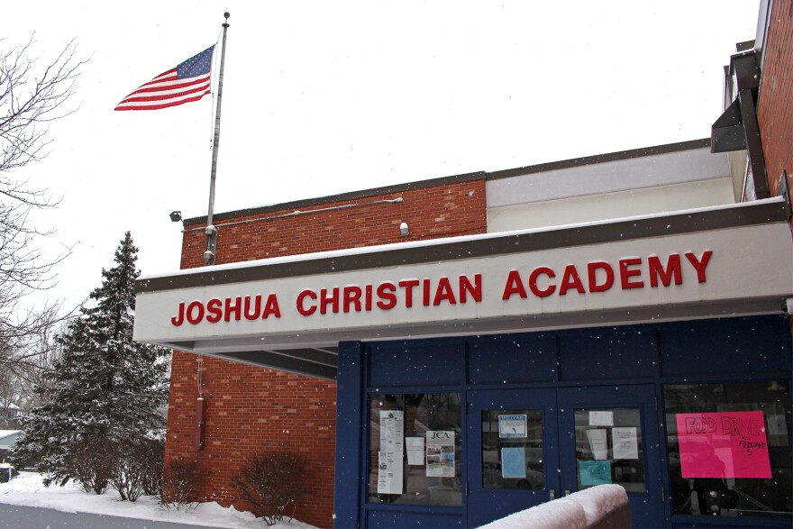 Snow falls on the front entry to Joshua Christian Academy school in Des Moines.