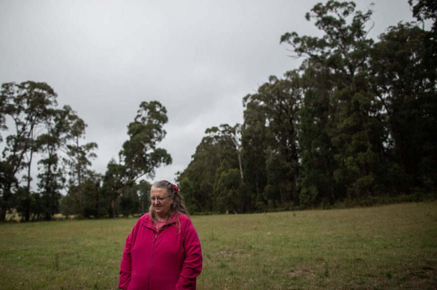 """Christine Stonehouse stands next to the site of her former home, which burned down on Black Saturday in 2009. """"Our plan was always to leave,"""" she says of her family's decision to flee as soon as it learned a bushfire was headed for its town."""