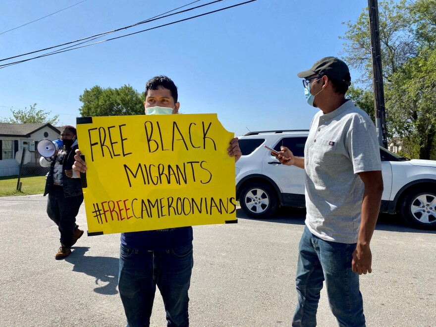 "Photo of a young man standing outside, wearing a face mask and holding a yellow sign that says ""Free Black Migrants #FreeCameroonians."""