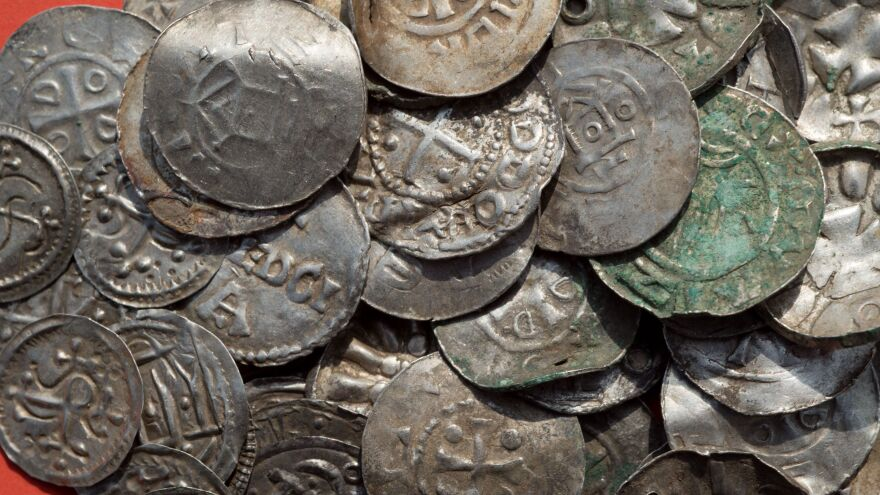 Saxon, Ottonian, Danish and Byzantine coins are pictured on a table in Schaprode, northern Germany on April 13, 2018.  Hundreds of coins — some split apart — were located in the dig, along with braided necklaces, pearls, brooches, a Thor's hammer and rings.
