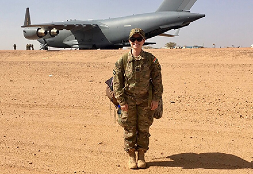 female U.S. Air Force nurse in the desert in front of a cargo plane
