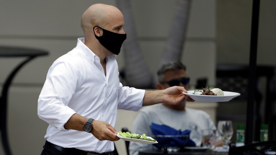 A food server wears a protective face mask as he delivers food to customers.