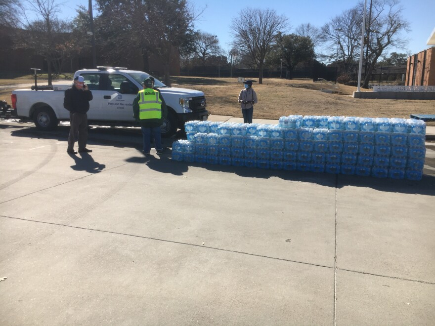 IMG_5189.JPG Wrapped, plastic water bottles stacked in an orderly array with some volunteers to the left, in front of a white City of a Dallas pickup truck