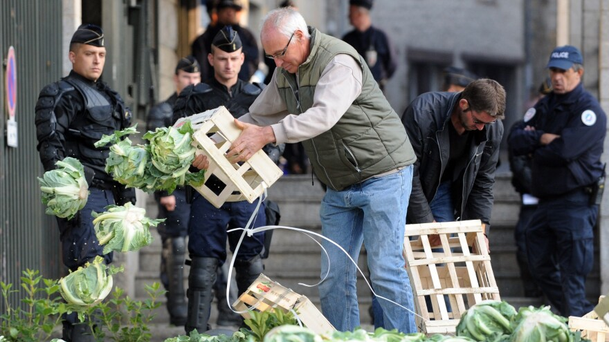 A farmer protesting falling prices dumps cauliflower in front of the prefecture building of Saint-Brieuc in northwestern France as police look on Sept. 24.