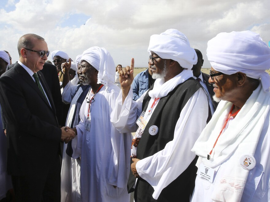 Turkey's President Recep Tayyip Erdogan shakes hands with local people in Port Sudan, Sudan, on Dec. 25, one of many locations in Africa the Turkish leader has visited recently.