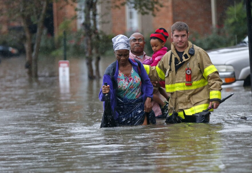 A member of the St. George Fire Department assists residents as they wade through floodwaters from heavy rains in Baton Rouge, La., on Friday.