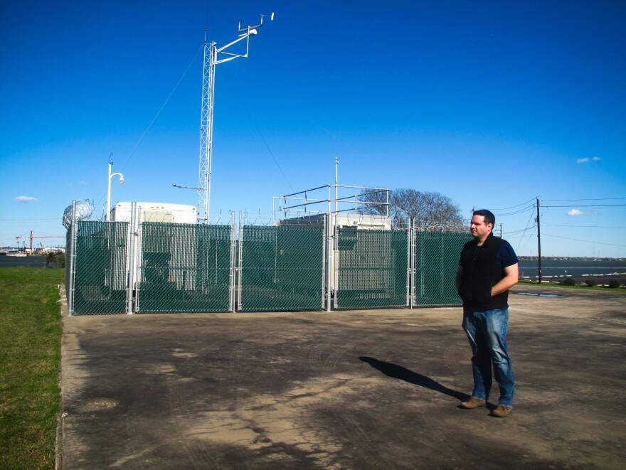Matthew Tejada stands near an air monitoring station.