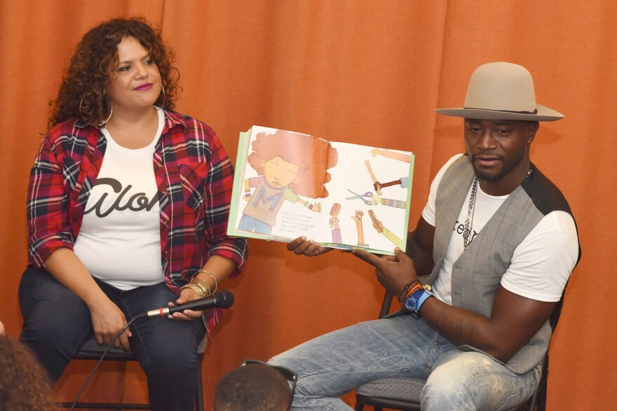 Fashion designer Sonia Smith-Kang sits with actor Taye Diggs as he reads his book, <em>Mixed Me</em>, to children in Los Angeles in 2015.