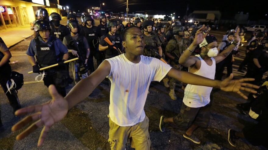 Protesters walk in front of a line of police early Wednesday as authorities try to disperse a demonstration in Ferguson, Mo. The St. Louis suburb saw less violence than on other recent nights of protests.