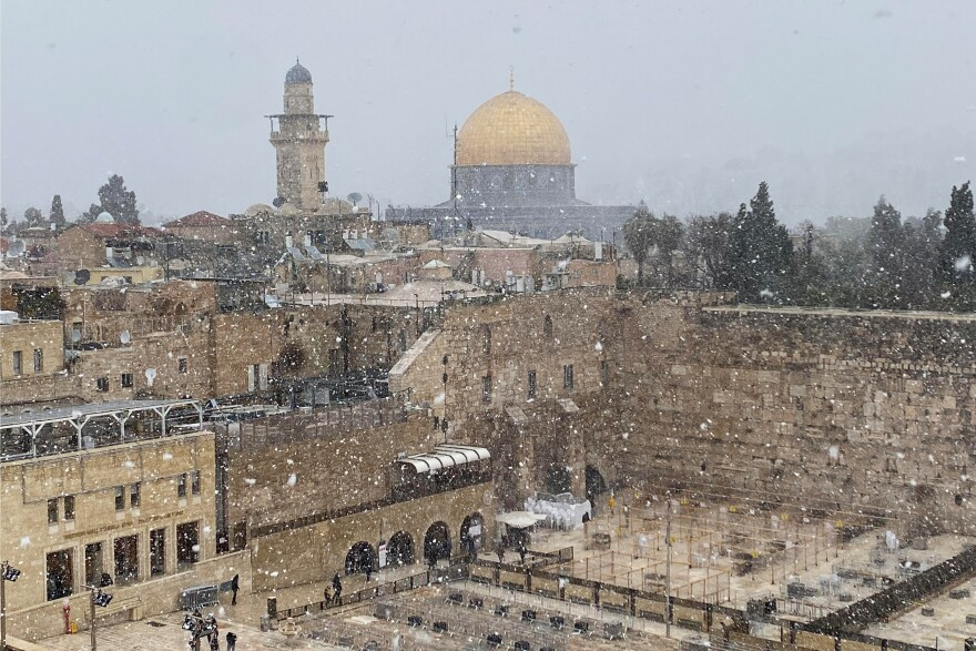 A general view of Jerusalem's Old City shows the Western Wall in the foreground and the Dome of the Rock in the background, as the snow starts to fall in Jerusalem on Wednesday.
