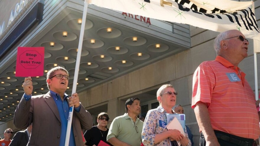 Gordon Martinez (left), leader of the group Faith in Texas and payday loan borrower, marches before a Consumer Financial Protection Bureau field hearing in Kansas City, Mo., on June 2.