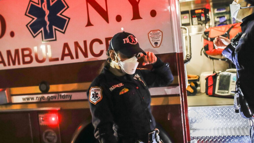 New York City Fire Department paramedic Elizabeth Bonilla (center) wears personal protective equipment after an emergency call in April in the Bronx borough of New York City. Bonilla is suing the city for allegedly retaliating against her and other EMS workers who spoke to the news media about responding to the COVID-19 pandemic.