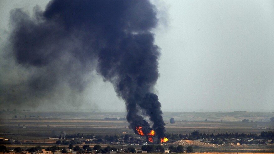 In this photo taken Thursday, flames and smoke billow from a fire on a target in Ras al-Ayn, Syria. This is the result of shelling by Turkish forces, the same day Turkey and the U.S. were negotiating a cease-fire agreement.