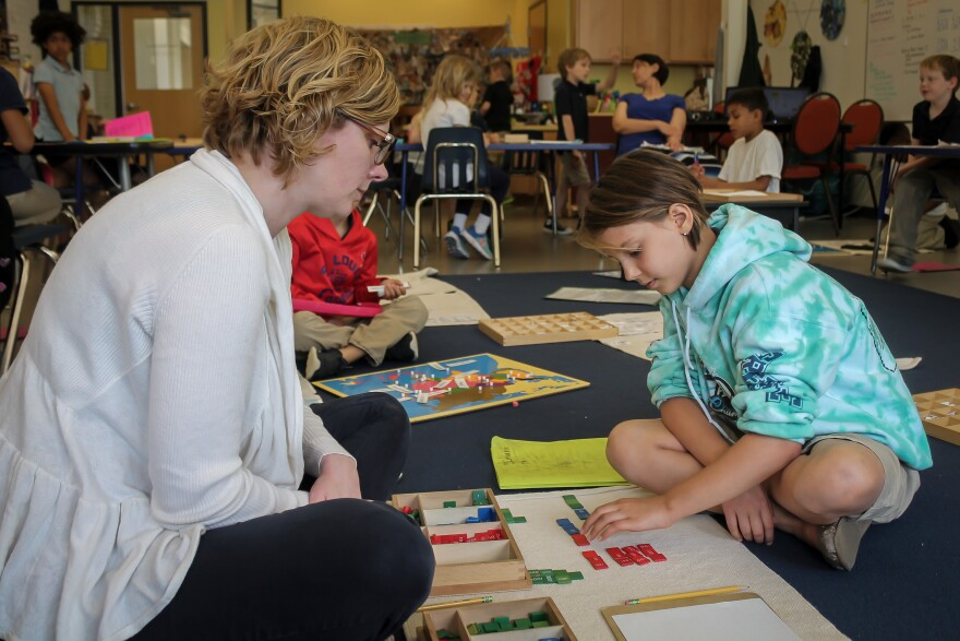 City Garden Montessori teacher Anne Lacey works with student Imani Palada, 8, on math problems in April 2017..