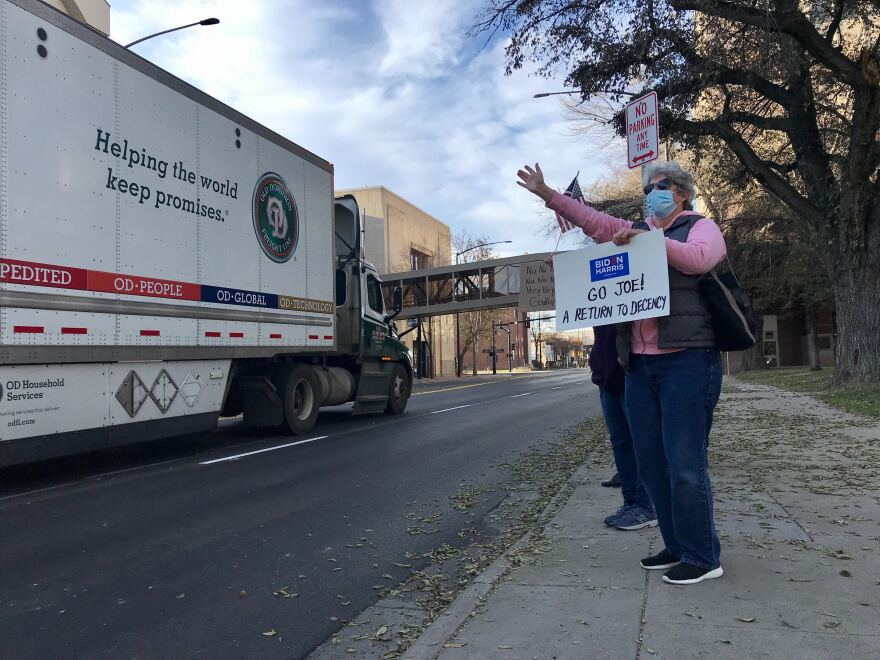 """A woman stands on the side of 27th St. in downtown Billings holding a homemade sign that reads """"Go Joe! A return to decency."""""""