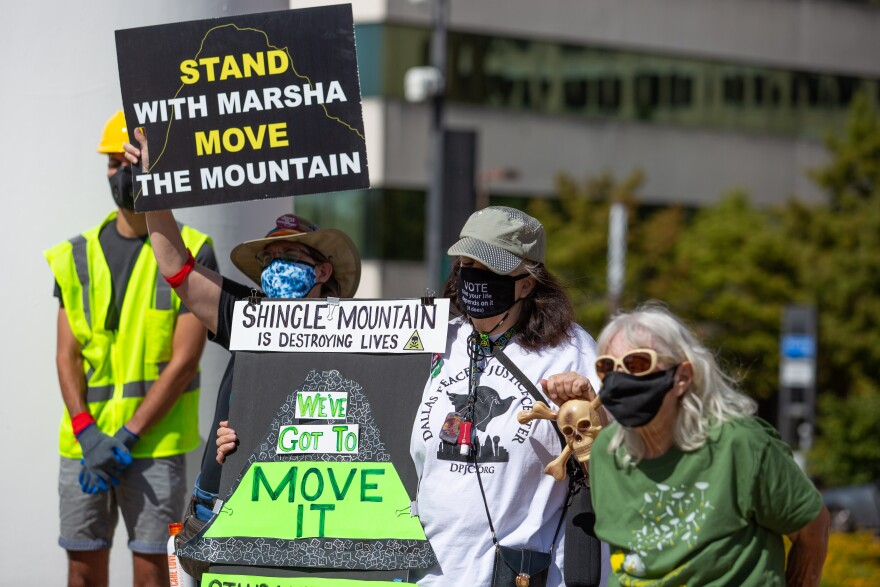 Environmental activists hold signs to demand the relocation of Shingle Mountain, at the action event at Dallas City Hall.