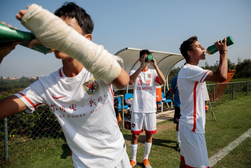 Brazilian and Chinese players drink water during a practice break.