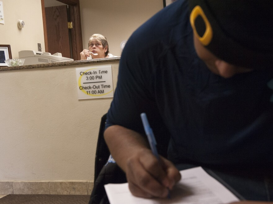Bazileo Hernandez (right) fills out a job application at a motel while searching for jobs in Williston, N.D., in January.