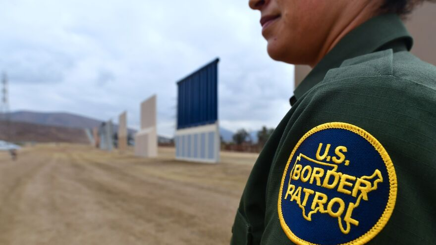 A U.S. Border Patrol officer stands near prototypes of President Trump's proposed border wall in San Diego last November.
