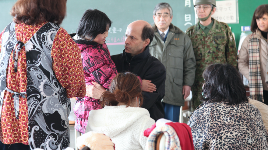 In a photo from March 2011, then-U.S. Ambassador to Japan John Roos visits the Tohoku region, hardest hit by the tsunami and earthquake. He and his team then started the Tomodachi (Friends) Initiative to help young survivors.