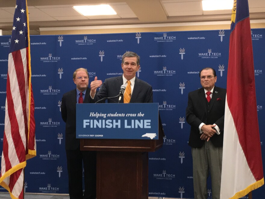 Governor Roy Cooper announced the Finish Line Grants Program from the campus of Wake Technical Community College. He is flanked by the state community college President Peter Hans on his left, and Wake Technical Community College President Stephen Scott.