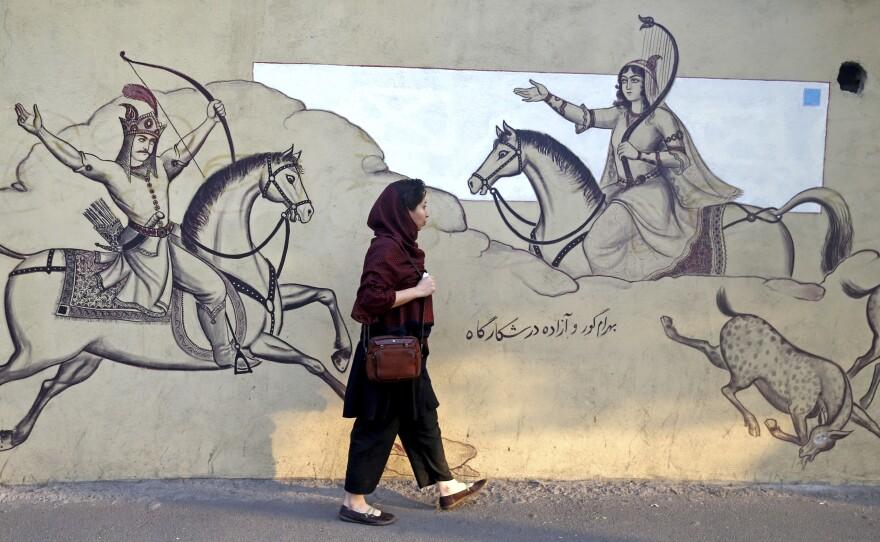 An Iranian woman walks past a wall mural last month in downtown Tehran, Iran.