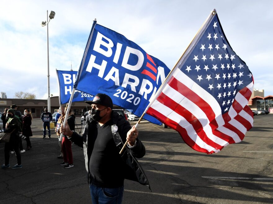 Chris Vela of Nevada carries a Biden-Harris flag and an American flag as supporters of Joe Biden prepare to hold a car parade to celebrate the outcome of Tuesday's election on in Las Vegas, Nevada.