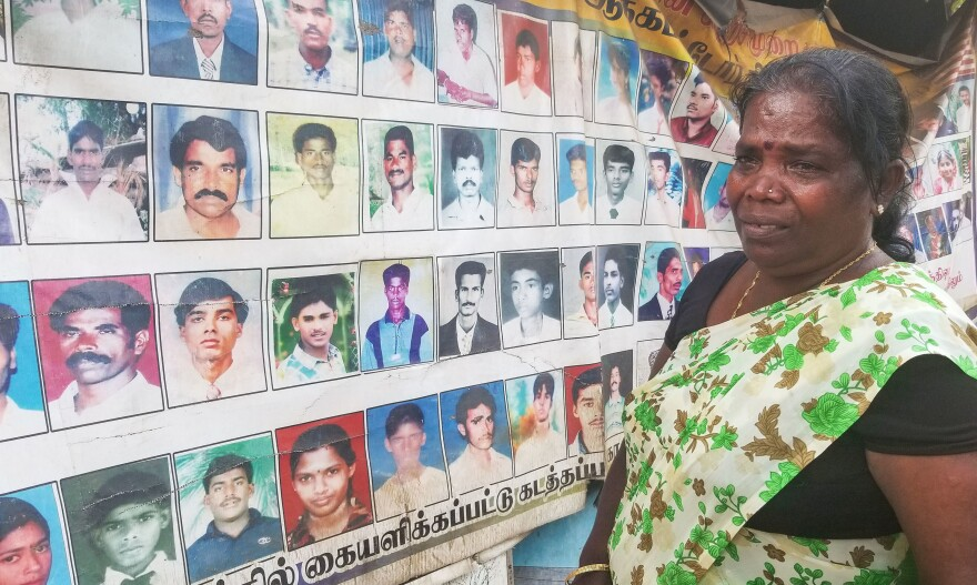 Rajandran Barathamatha, 55, stands outside a protest tent in Vavuniya, Sri Lanka covered with photos of some of the tens of thousands of peoe who went missing in Sri Lanka's 26-year civil war. Her son was among them.