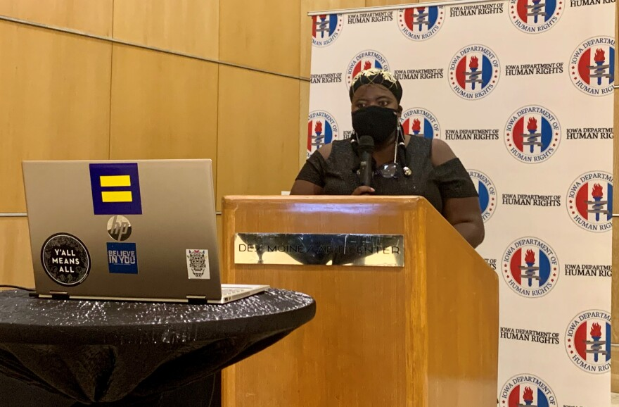 A woman stands behind a podium wearing a black mask and holding a microphone.