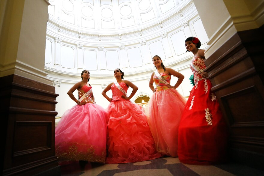 Four young women in Quinceñera dresses pose at the Texas Capitol.