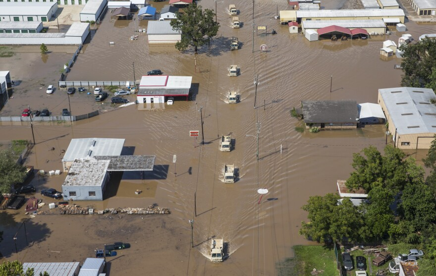 National Guard vehicles drive down a flooded street in Wharton, Texas, on Friday.