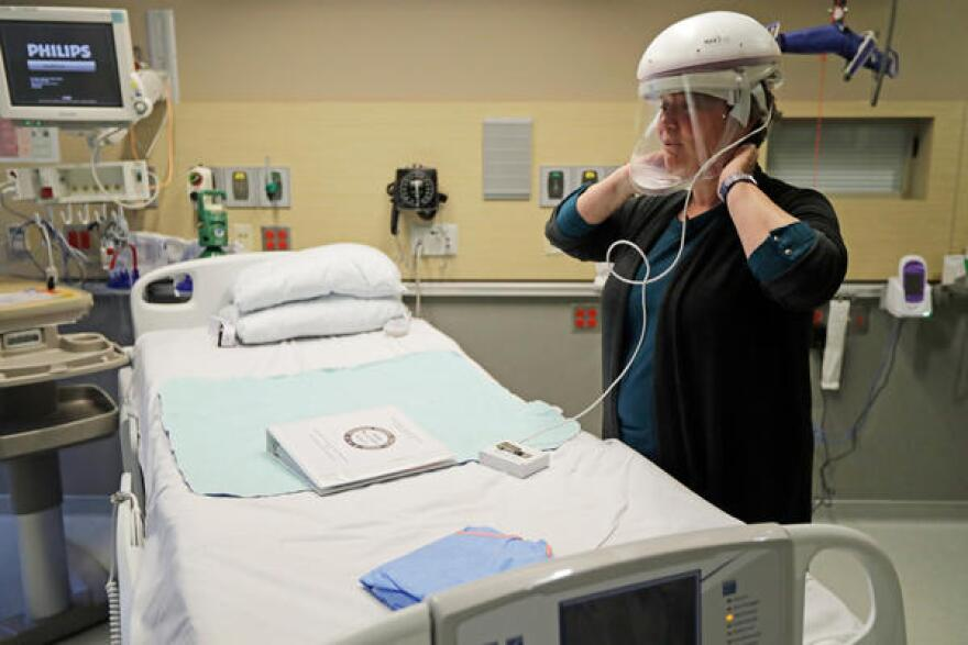 The first U.S. case of COVID-19 was treated at Providence Regional Medical Center in Everett, Washington. Robin Addison, a nurse there, demonstrates how she wears a respirator helmet with a face shield intended to prevent infection.
