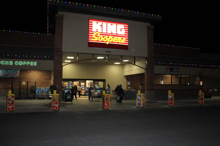 The front of a King Soopers grocery store, lit up at night, with shoppers walking in and out of the entrance.