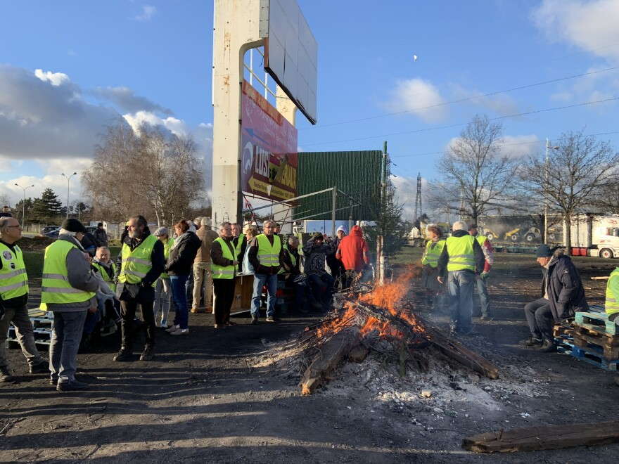 Yellow vest protesters keep a bonfire going at a traffic circle near the city of Rouen in Normandy, France.