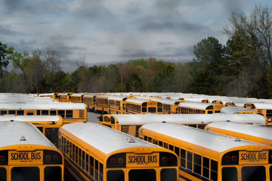 School buses sit parked at a lot in Marietta, Ga., in March. Georgia Gov. Brian Kemp has pushed for students to return to school in the fall, but the state's largest system, in Gwinnett County, has decided on all-virtual learning.