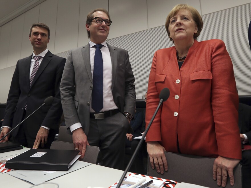 German Chancellor Angela Merkel, right, and the chairman of the German Christian Social Union state group, Alexander Dobrindt, center, arrive for a faction meeting at the Bundestag, in Berlin, on Monday.