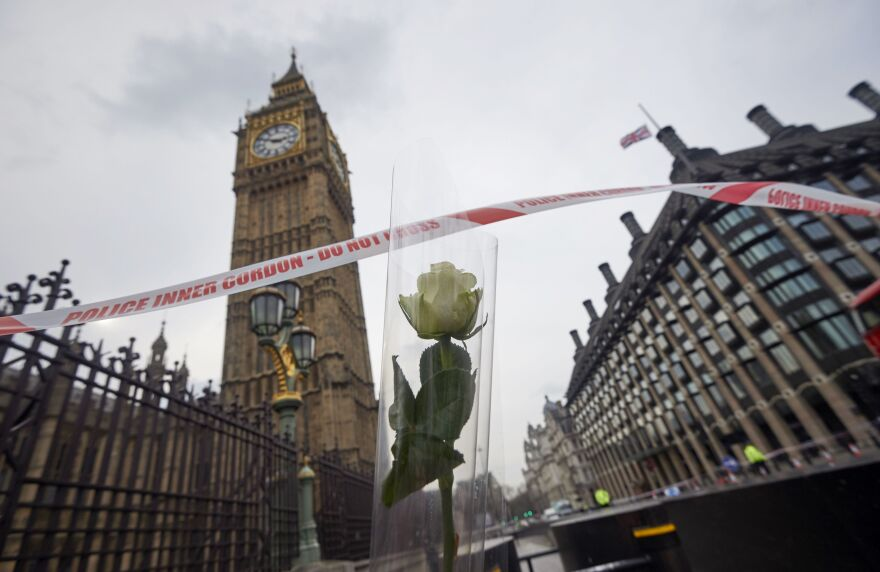 A flower left in tribute to the victims of Wednesday's attack is seen next to the Palace of Westminster that houses the Houses of Parliament in central London.