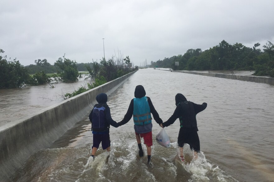 Three Galvan cousins hold hands as they walk on the flooded highway.