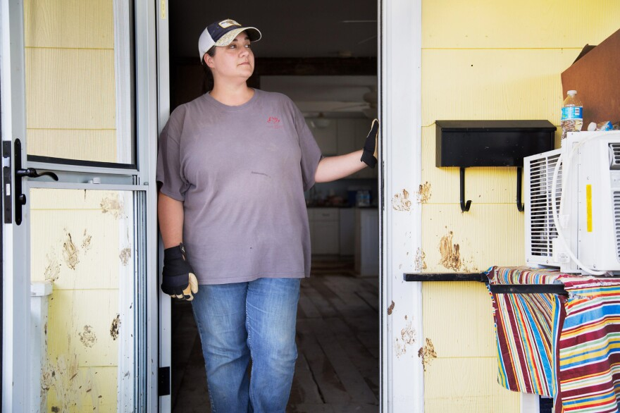 Rachel Taylor surveys the flood damage from her front porch in White Sulphur Springs, W.Va. Muddy paw prints on the front door still mark her dog's panic as the waters rose. He survived, but others didn't.