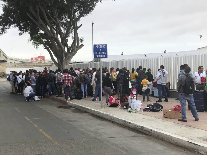 Asylum seekers in Tijuana, Mexico, listen to names being called from a waiting list to claim asylum at a border crossing in San Diego on Sept. 26.