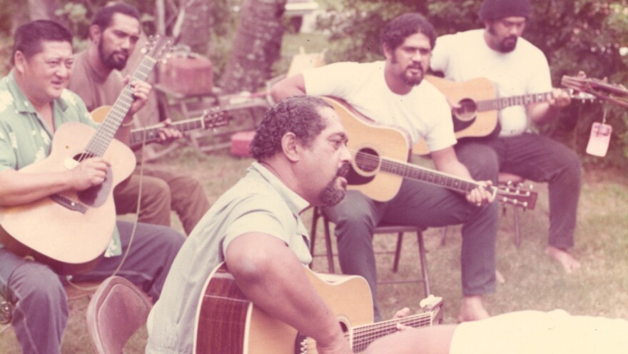 "Gabby Pahinui (center), playing in his family's backyard with (from left to right) Leland ""Atta"" Isaacs, Philip Pahinui, Cyril Pahinui and Martin Pahinui. This photo is in the album insert for the 1972's <em>Gabby</em>."