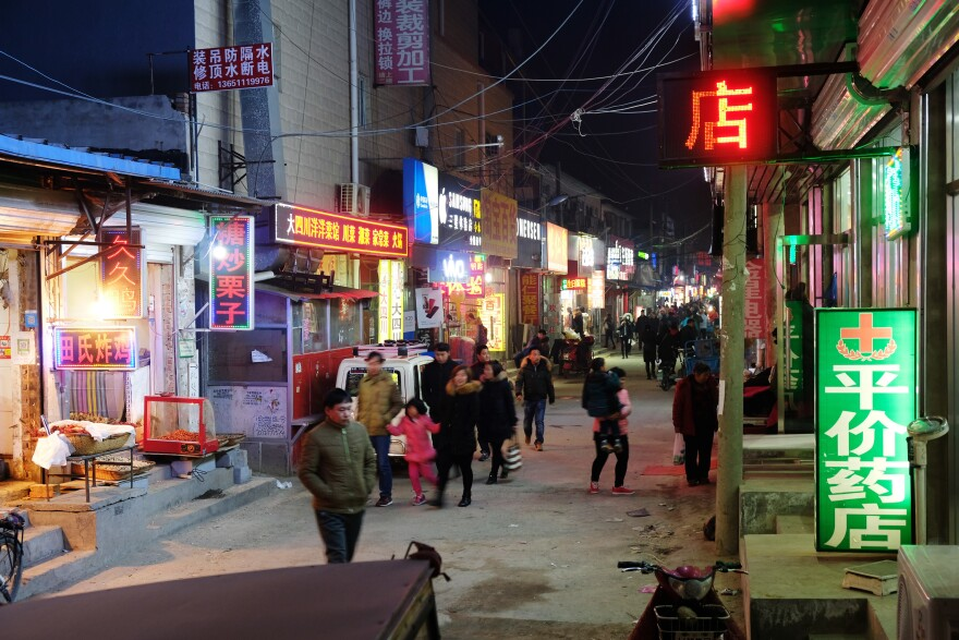 People walk on a street in a Beijing migrant enclave, part of which has been slated for demolition.