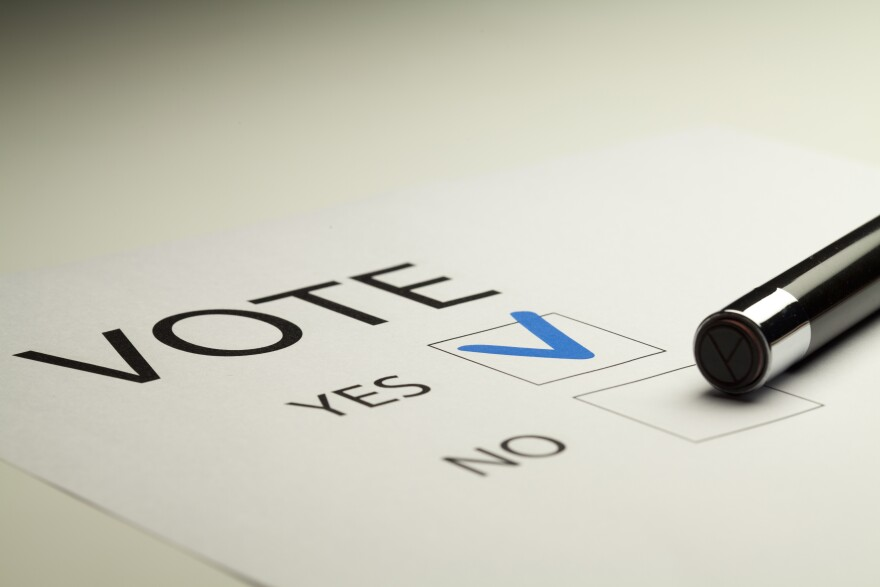 A paper with the word Vote and two boxes that say Yes or No. The Yes box has a marking in it.