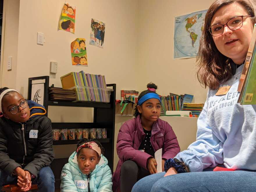 """UNC Greensboro education student Shelby Morris reads """"Freedom On The Menu"""" to a Girl Scout troop visiting the International Civil Rights Center and Museum."""