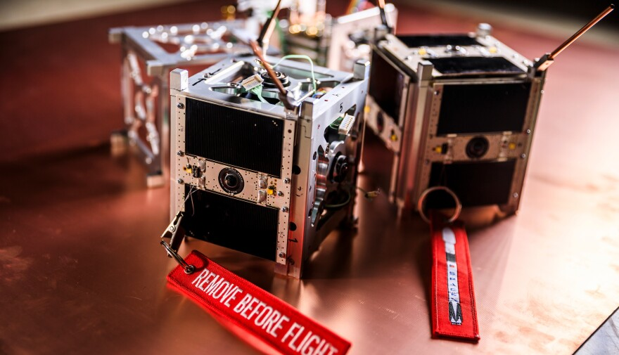 A photo of  small, metal cubes with cameras mounted on all six sides