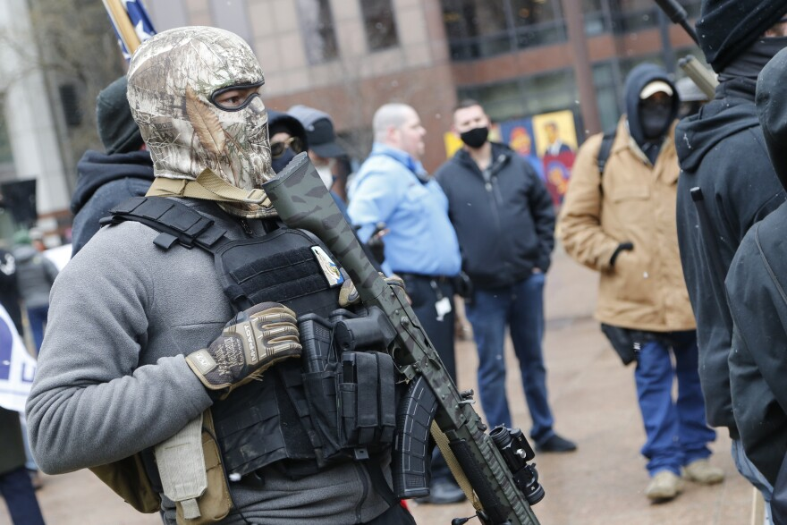 An armed protestor stands outside the Ohio Statehouse Sunday, Jan. 17, 2021, in Columbus, Ohio.