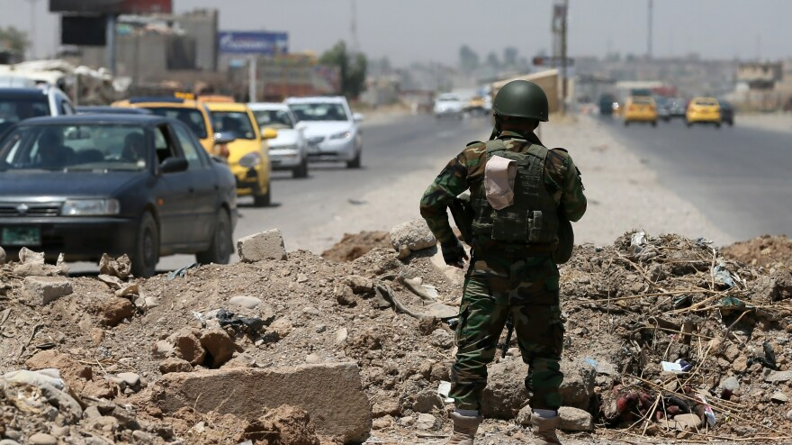 A decade ago, U.S. soldiers were fighting and rebuilding in the Iraqi cities of Mosul and Tikrit. The past few weeks have seen those cities, among others, fall to the Sunni militant group ISIS. Here, a member of the Kurdish Peshmerga forces stands guard Thursday near an ISIS checkpoint in Mosul.